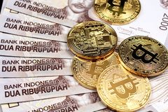 A close up image of Indonesian 2000 rupiah notes with gold bitcoins. Indonesian 2000 rupiah bank notes shot close up with golden bitcoins Stock Photo