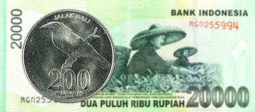 200 indonesian rupiah coin against 20000 indonesian rupiah note stock images