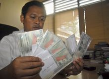 INDONESIAN RUPIAH SIX YEARS LOW DROP. Police commissioner Syarif Rahman shows a set of fake Rupiah notes in Solo, Java, Indonesia. The Indonesian currency Rupiah stock photos