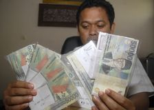 INDONESIAN RUPIAH SIX YEARS LOW DROP. Police commissioner Syarif Rahman shows a set of fake Rupiah notes in Solo, Java, Indonesia. The Indonesian currency Rupiah royalty free stock photos