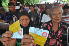 Indonesian Social Protection Card. Poor people Social Protection Card show while queuing take help in cash money at the Office of Pos, Solo, . The card is one of Royalty Free Stock Photography