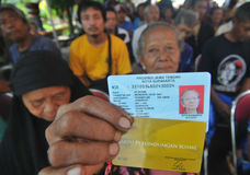 Indonesian Social Protection Card. Poor people Social Protection Card show while queuing take help in cash money at the Office of Pos, Solo, . The card is one of Royalty Free Stock Image