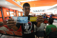 Indonesian Social Protection Card. Poor people Social Protection Card show while queuing take help in cash money at the Office of Pos, Solo, . The card is one of Stock Photos