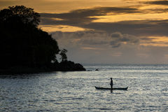 Indonesian Sunset. A boat silhouetted against a glorious Indonesian sunset near the remote Ambon Island in the Indonesian archipelago stock photo