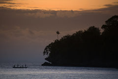 Indonesian Sunset. A boat silhouetted against a glorious Indonesian sunset near the remote Ambon Island in the Indonesian archipelago stock photos