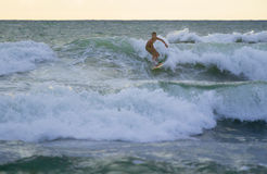 Indonesian surfer surfing in Kuta on Bali. Kuta, Indonesia - January 26, 2014: Indonesian surfer surfing in Kuta on Bali, Indonesia Stock Image