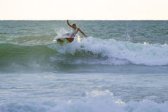 Indonesian surfer surfing in Kuta on Bali Stock Image