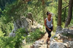 Tourist watching on rock by Thomas´s View in Slovak Paradise. Indonesian tourist - smiling young Papuan girl standing on rock near by viewpoint Thomas´s royalty free stock images
