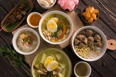 Indonesian traditional food. Lontong sayur with bakso soto and bubur ayam on a table stock photo