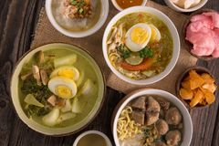Indonesian traditional food. Lontong sayur with bakso soto and bubur ayam on a table stock photography