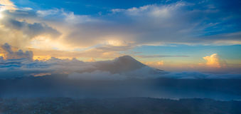Indonesian Volcano Agung in Bali island. Mountain landscape in tropical panorama. A couple hours Just after Sunrise hike with fluffy white clouds. Viewpoint royalty free stock photo