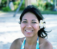 Indonesian Woman. Indonesian beauty with a Frangipani flower in her hair looks out to the ocean royalty free stock image