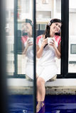 Indonesian woman enjoying music at home with coffee Stock Images