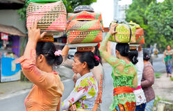 Indonesian women carry offerings in baskets Royalty Free Stock Photo