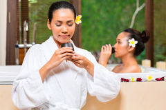 Indonesian women having wellness bath drinking tea. Indonesian Asian women in wellness beauty day spa having aroma therapy bath and drinking herbal tea for detox Royalty Free Stock Photos