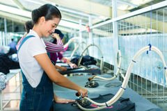 Indonesian worker with flat iron in textile factory. Female Asian worker irons a print on a shirt or a T-Shirt in a Indonesian textile factory Royalty Free Stock Photos