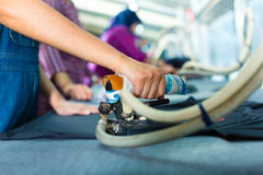 Indonesian worker with flat iron in textile factory Stock Photography