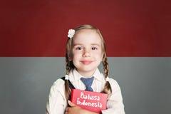 Indonesien begrepp med ungeliten flickastudenten med den röda boken mot den indonesiska flaggabakgrunden Lär det indonesiska språ royaltyfri foto