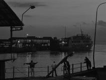 Indonesien - fiskare i mjukt ljus och färja i bakgrunden Arkivfoton