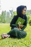 Indonesisch moslimmeisje met een quran Stock Afbeeldingen