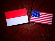 Indonesische Flagge mit USA-Flagge auf einem Baumstumpf lokalisiert lizenzfreies stockbild