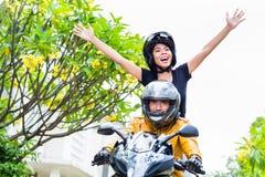 Indonesische Frau, die frei auf Motorrad glaubt Stockfotografie