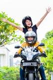 Indonesische Frau, die frei auf Motorrad glaubt Lizenzfreies Stockbild