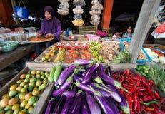 Indonesische Frau, die Gemüse im Markt bei Timika verkauft. Lizenzfreie Stockfotos