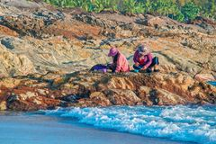 Indonesische Frauen sortieren den Fischereifang, indem sie auf einem Felsen durch das Meer am Abend sitzen Küste des Schwarzen Me lizenzfreies stockfoto