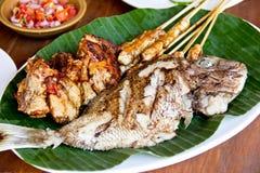 Indonesische Küche, gebratene Fische, Satay-Hühneraufsteckspindeln und gebratene Hühnerbrust Stockbilder