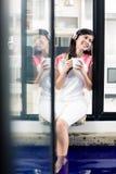 Indonesische vrouw die van muziek thuis met koffie genieten Stock Afbeeldingen