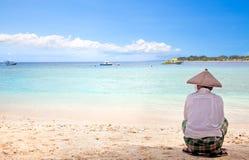 Indonesischer Mann mit dem Strohhut, der auf dem Strand sitzt Lizenzfreie Stockbilder