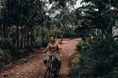 Indonesisk man som rider en motorcykel royaltyfri bild