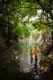 Indonesiska män som muddrar en flod, Jakarta, Indonesien Arkivfoton