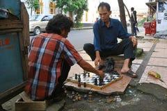 Indonesiska män som spelar schack i gatan Arkivfoton