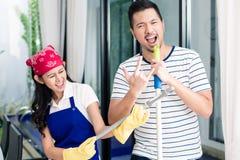 Indonesiska par som har gyckel som gör ren hemmet Royaltyfria Foton