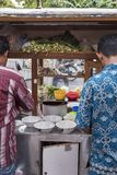 Indonezja mężczyźni przygotowywają jedzenie przy rocznika pchnięcia drewnianą uliczną karmową furą w Dżakarta, Indonezja obraz royalty free