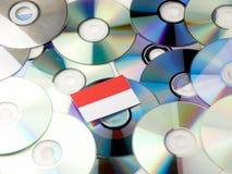 Indonezyjczyk flaga na górze cd i DVD stosu odizolowywającego na bielu Fotografia Stock