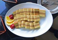 Indonezyjscy kueh lapis słuzyć na białym talerzu z rżniętymi owoc na stronie Fotografia Stock