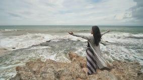 Indonezyjska dziewczyna cieszy się życie z szeroko rozpościerać rękami na skalistym brzeg na wyspie Bali zbiory wideo