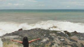 Indonezyjska dziewczyna cieszy si? ?ycie z szeroko rozpo?ciera? r?kami na skalistym brzeg na wyspie Bali zbiory