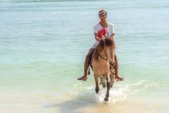 Indonezyjski mężczyzna jedzie konia na plaży Obrazy Royalty Free