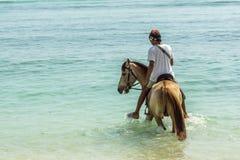 Indonezyjski mężczyzna jedzie konia w płytkiej wodzie blisko do Zdjęcie Stock