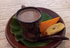Indonezyjski tradycyjny napoju ` bajigur ` słuzyć z gotowanym bananem i batatem zdjęcia royalty free