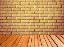 Indoor background with yellow brick wall and wooden plank floor. Royalty Free Stock Photos