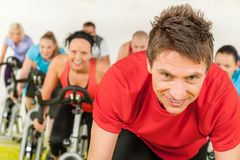 Indoor bicycle cycling in gym. People spinning in gym or fitness club exercise cardio training Stock Image