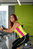 Indoor bicycle cycling in gym. Young Women spinning in the gym, exercising her legs doing cardio training Royalty Free Stock Image