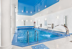Indoor big blue swimming pool interior Royalty Free Stock Image