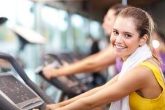 Indoor biking. Happy people doing indoor biking in a fitness club Stock Photography