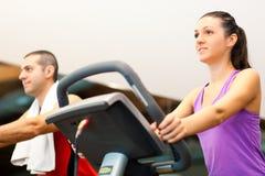 Indoor biking. Happy people doing indoor biking in a fitness club Royalty Free Stock Images